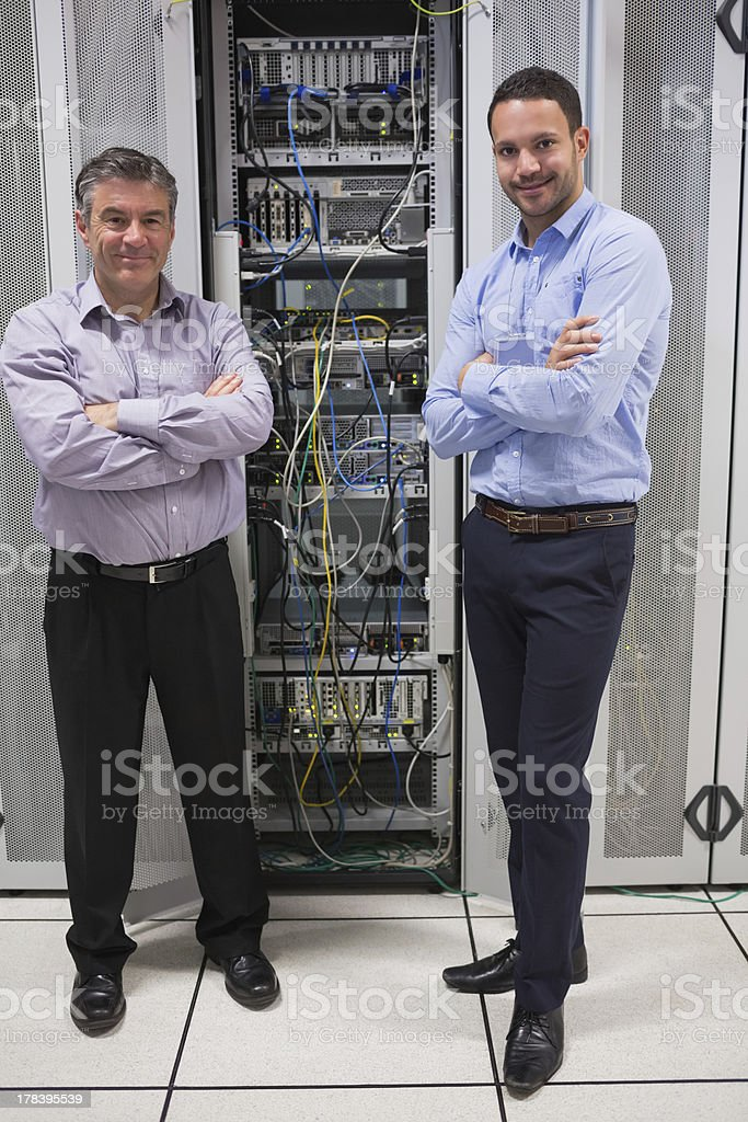 Two technicians standing in front of servers stock photo
