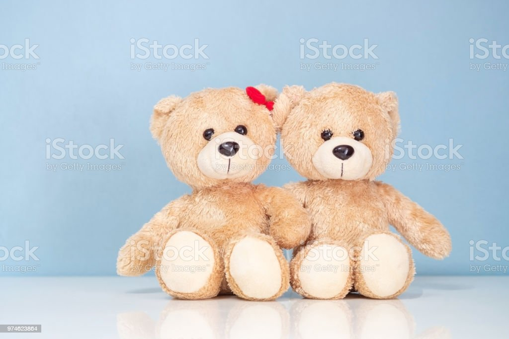 Two teddy Bear sitting on a white table and blue background. stock photo