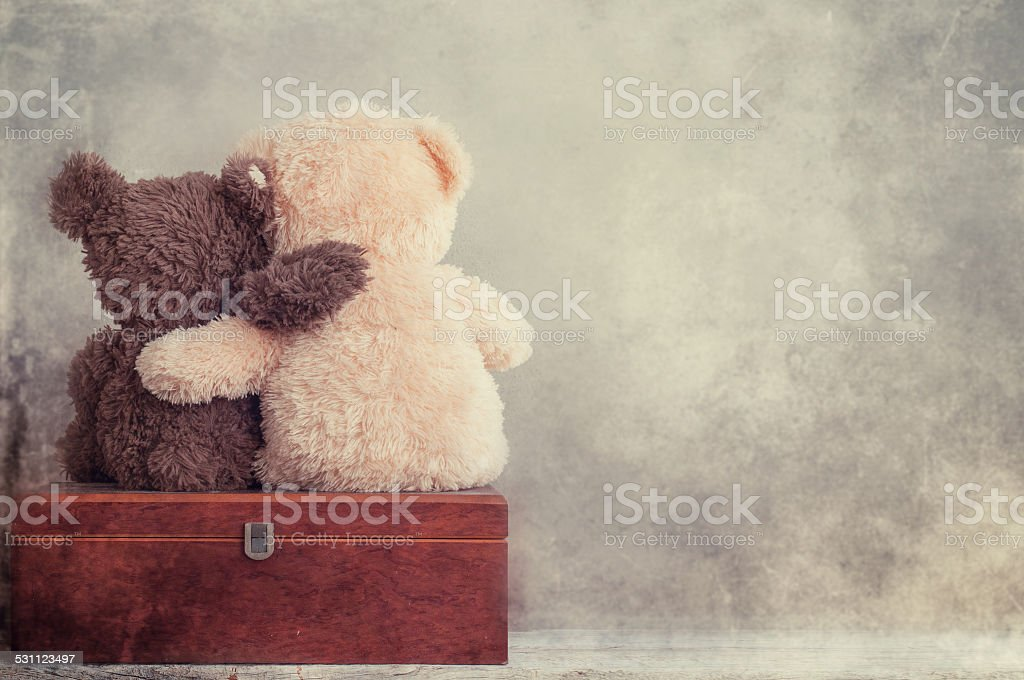 two teddy bears holding in one's arms stock photo