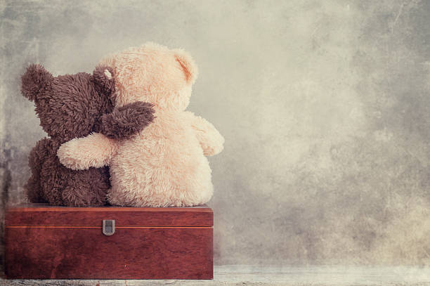 two teddy bears holding in one's arms - teddy bear stock photos and pictures