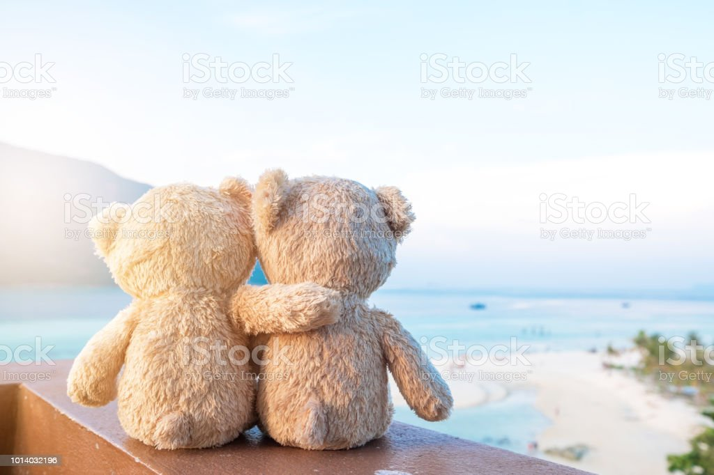 Two teddy bears sitting sea view. Love and relationship concept. Beautiful white sandy beach in the summer. stock photo