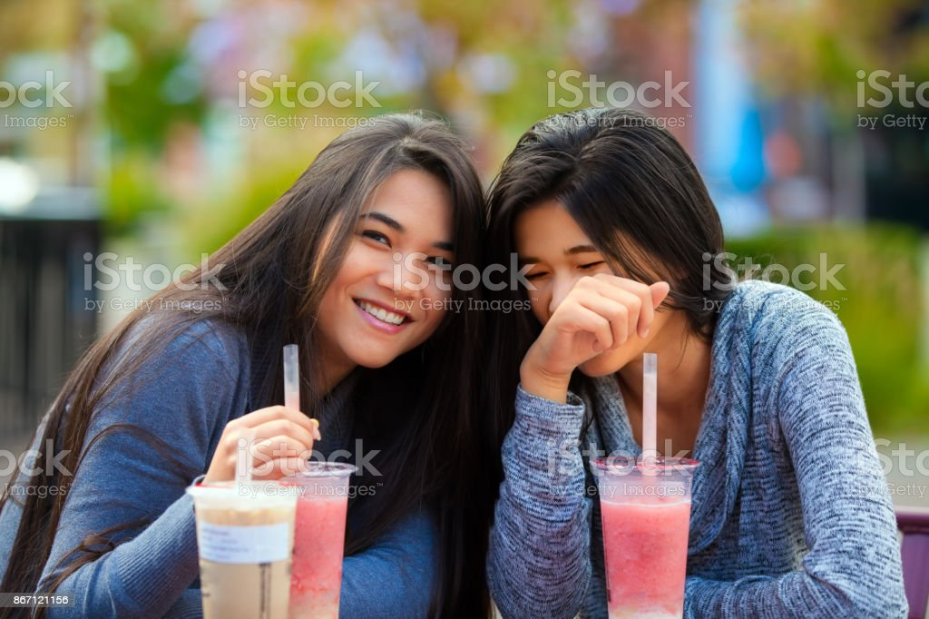 Two teen girls at outdoor cafe drinking boba tea together royalty-free  stock photo