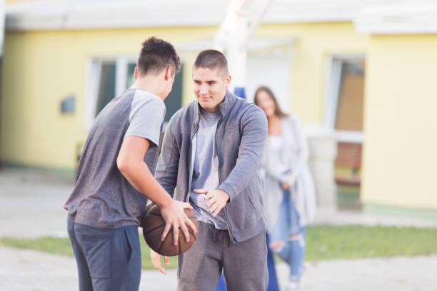 Two teenage boys playing basketball stock photo