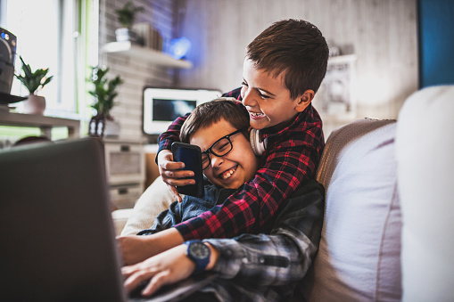 Two teenage boys with gadgets on couch at home