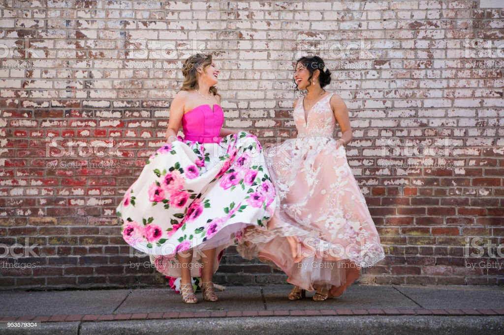 Two teenage girls dancing together outdoors stock photo