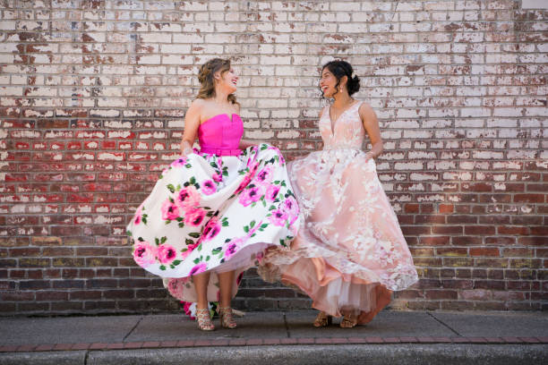 two teenage girls dancing together outdoors - prom stock photos and pictures
