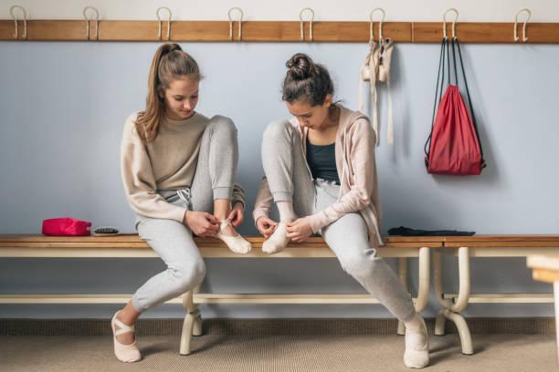 zwei mädchen im teenageralter dressing für ballett - sitzbank schuhe stock-fotos und bilder