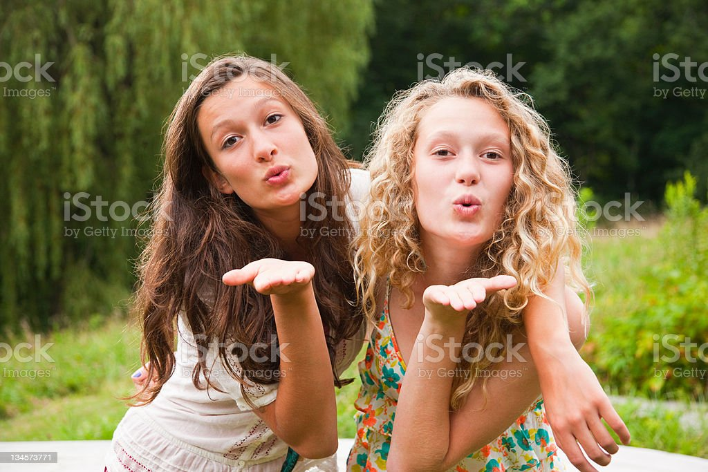 Two teenage girls fooling around in the countryside and blowing kisses stock photo