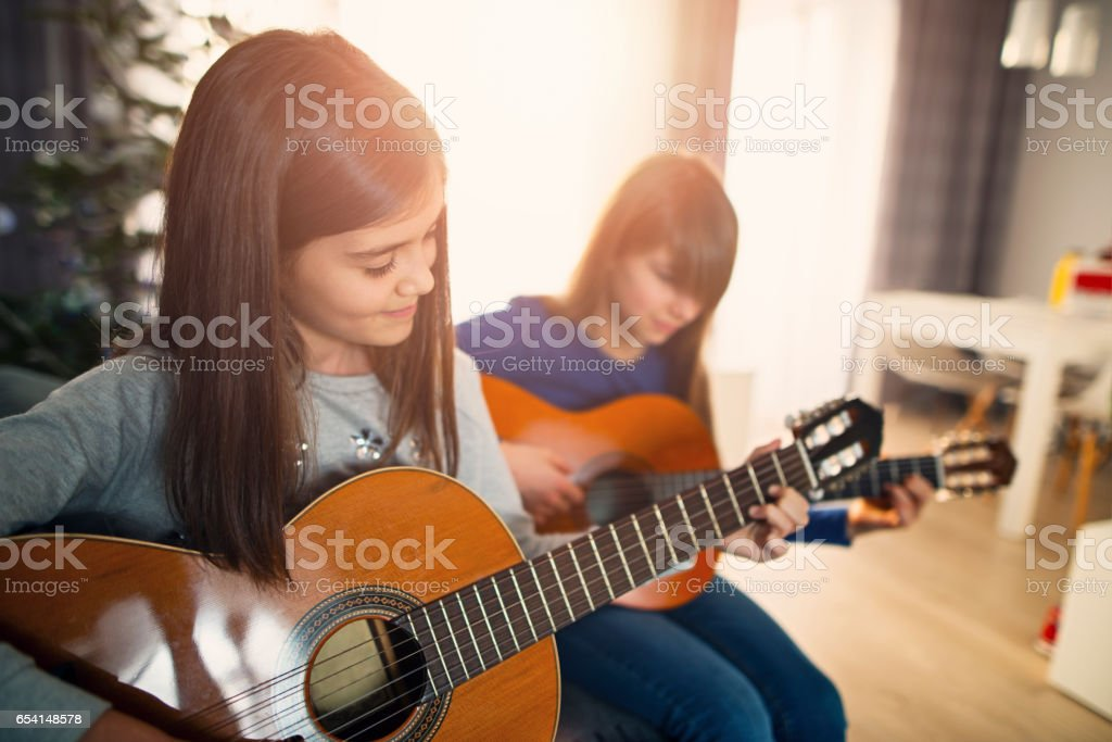 Two teenage girls having fun playing guitars together stock photo