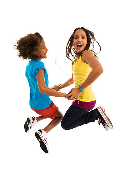 two teenage girls jumping mid air making a face - african youth jumping for joy stock photos and pictures