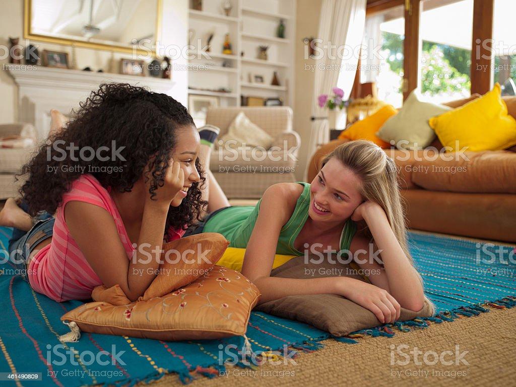 Two teenage girls lying down on floor talking royalty-free stock photo