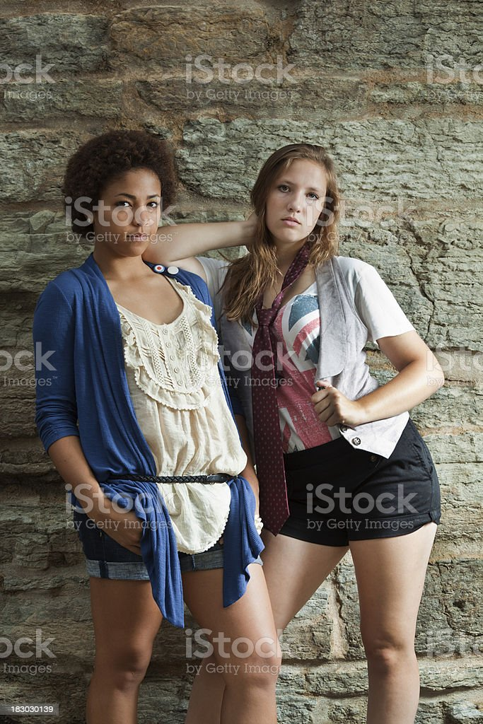 Two Teenage Girls Posing in Funky Clothes Against Stone Wall stock photo