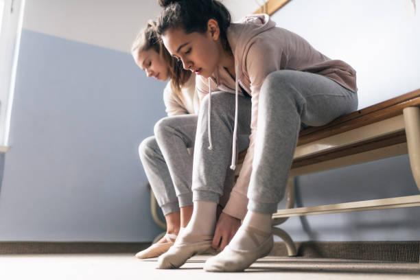 zwei mädchen im teenageralter auf schuhe für ballett - sitzbank schuhe stock-fotos und bilder
