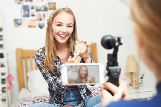 two teenage girls recording beauty blog in bedroom - vlogger stock photos and pictures