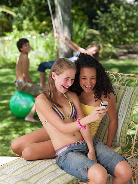Two teenage girls sitting outdoors in summer with cell phone smiling stock photo