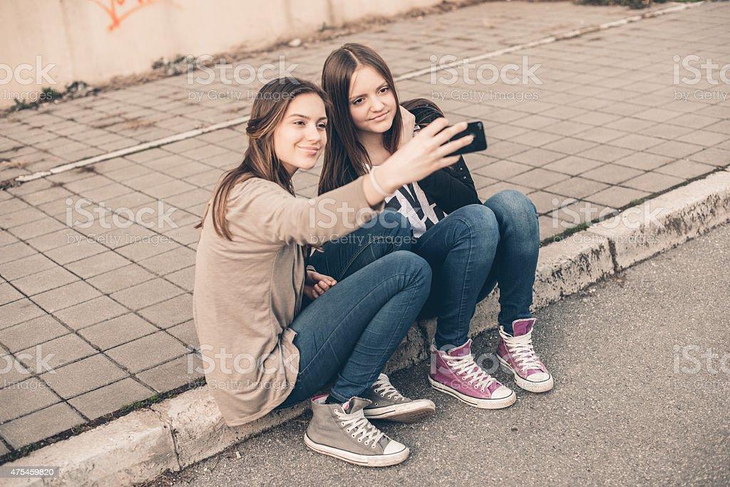 Two teenage girls sittnig at curb an make selfie stock photo