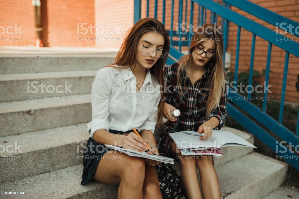 Two teenage girls studying in the school yard stock photo