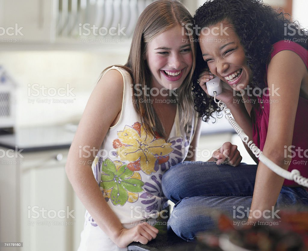 Two teenage girls talking on telephone laughing stock photo
