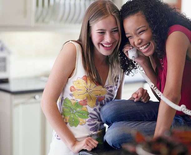 Zwei weibliche Teenager reden am Telefon lacht – Foto