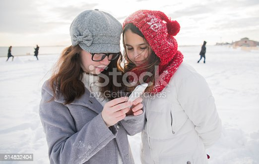 Two teenage girls looking for some info with the smartphome on the Brighton Beach covered by the snow. Brooklyn, New York City, USA