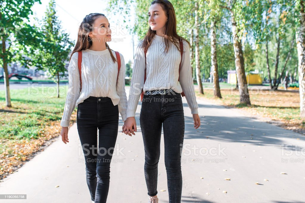 Two teenage girls walk in summer in park, talk, walk after school and college, hold hands, best friends return home after training. Free space for copy text. - Royalty-free Adult Stock Photo