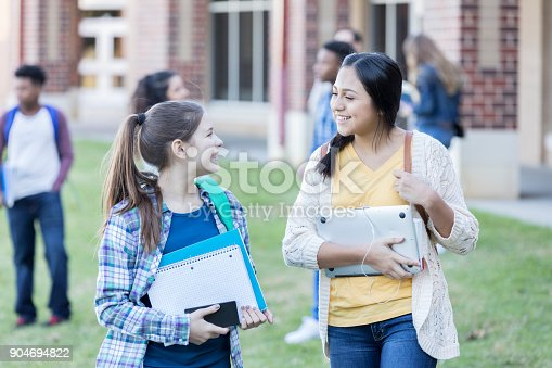 istock Two teenage girls walk together between classes outside 904694822