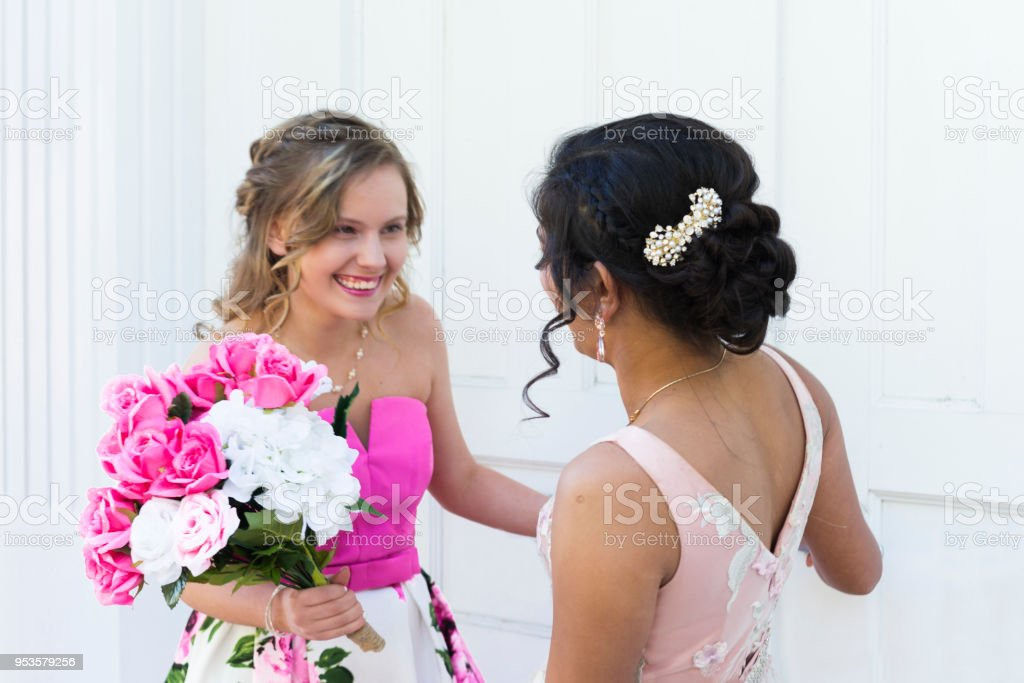 Two teenage girls wearing a formal party dresses having fun together  outdoors on a beautiful spring day, Indiana, USA - Stock image .