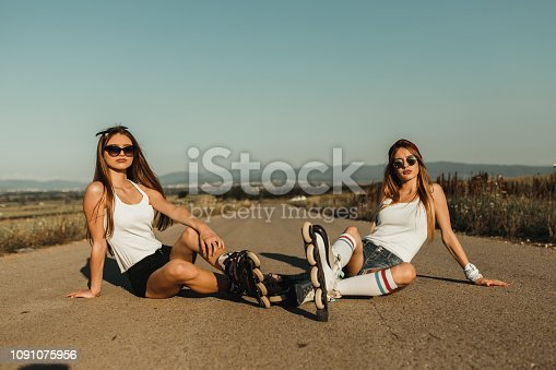 Two teenage girls with inline skates having fun on a sunny summer day