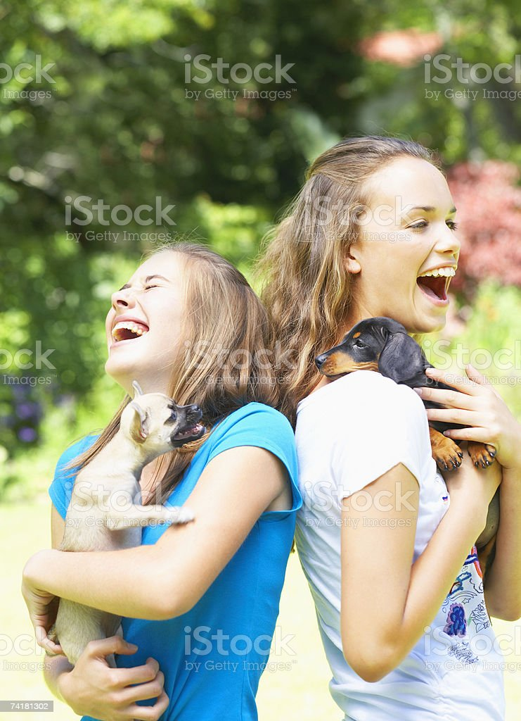 Two teenage girls with puppy dogs laughing