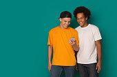 istock Two teenage guys using smatphone on blue background 1080967268