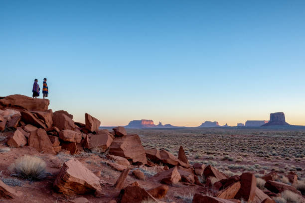 Two Teenage Native American Indian Navajo Sister in Traditional Clothing Enjoying the Vast Desert and Red Rock Landscape in the Famous Navajo Tribal Park in Monument Valley Arizona at Dawn stock photo