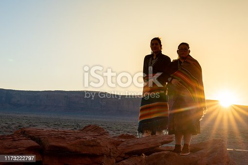 Two Teenage Native American Indian Navajo Sister in Traditional Clothing Enjoying the Vast Desert and Red Rock Landscape in the Famous Navajo Tribal Park in Monument Valley Arizona at Dawn