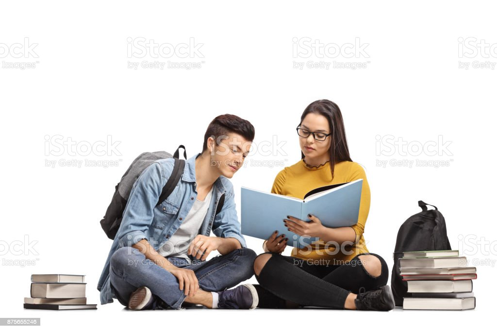 Two teenage students sitting on the floor and studying stock photo