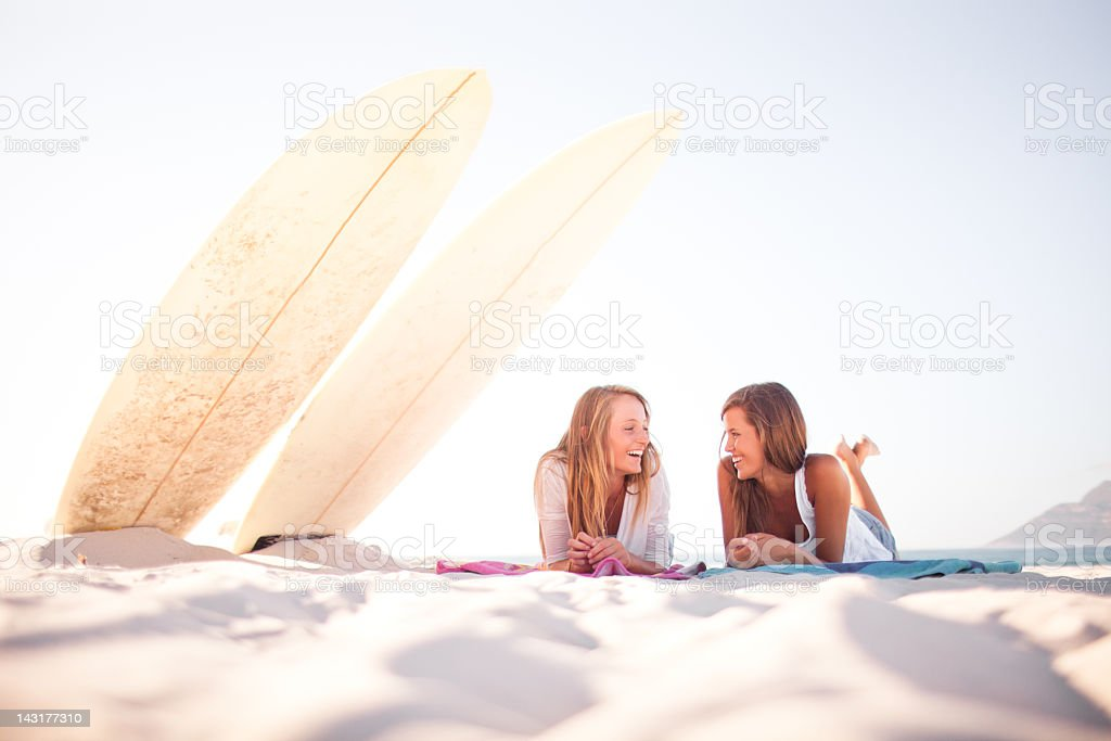 Two teenage surfer girls laughing and gossiping on the beach royalty-free stock photo