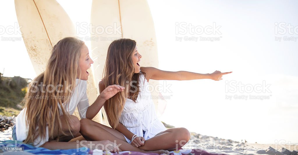 Two teenage surfer girls laughing and gossiping on the beach stock photo