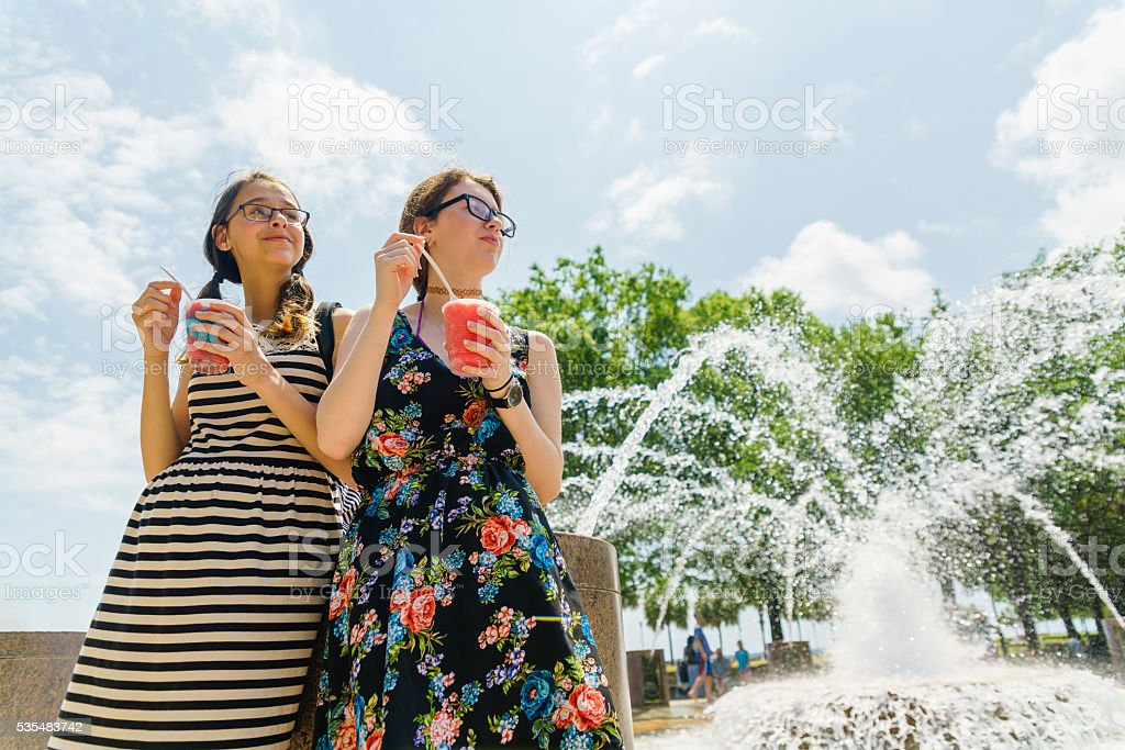 Two teenager girls eats icecream next to fountain in Charleston stock photo