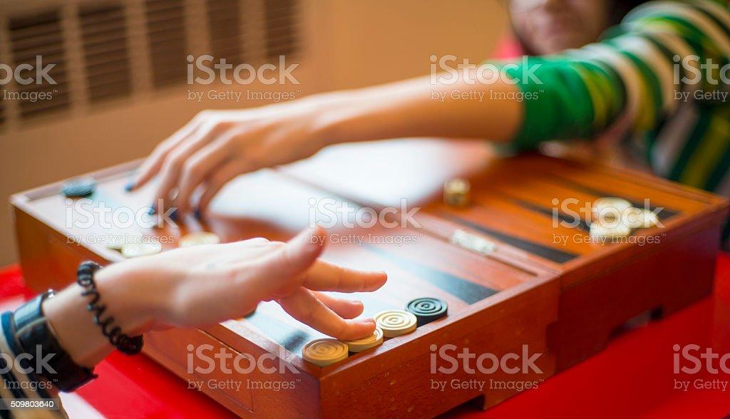 Two teenager girls playing backgammon stock photo