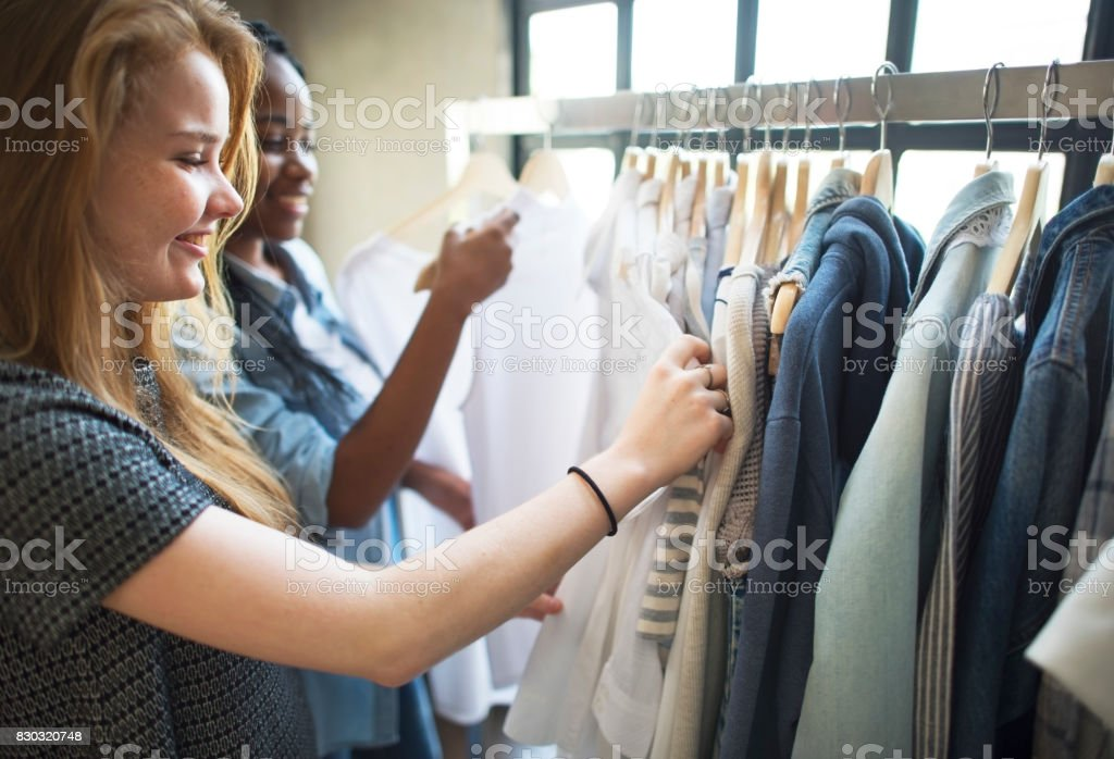 Two teenager girls selecting sloth in a shop stock photo