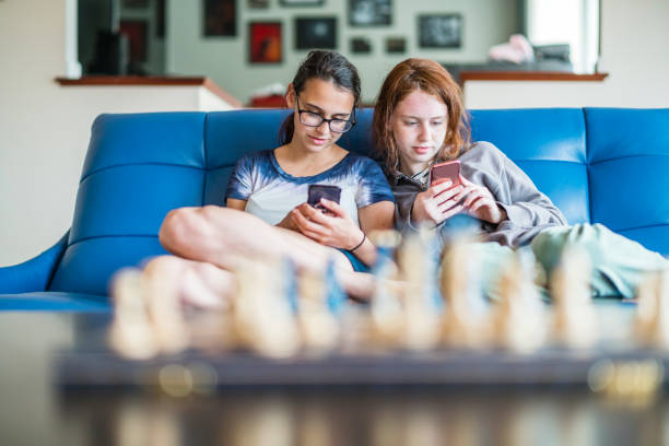 Two teenager girls, sisters, browsing social media together stock photo