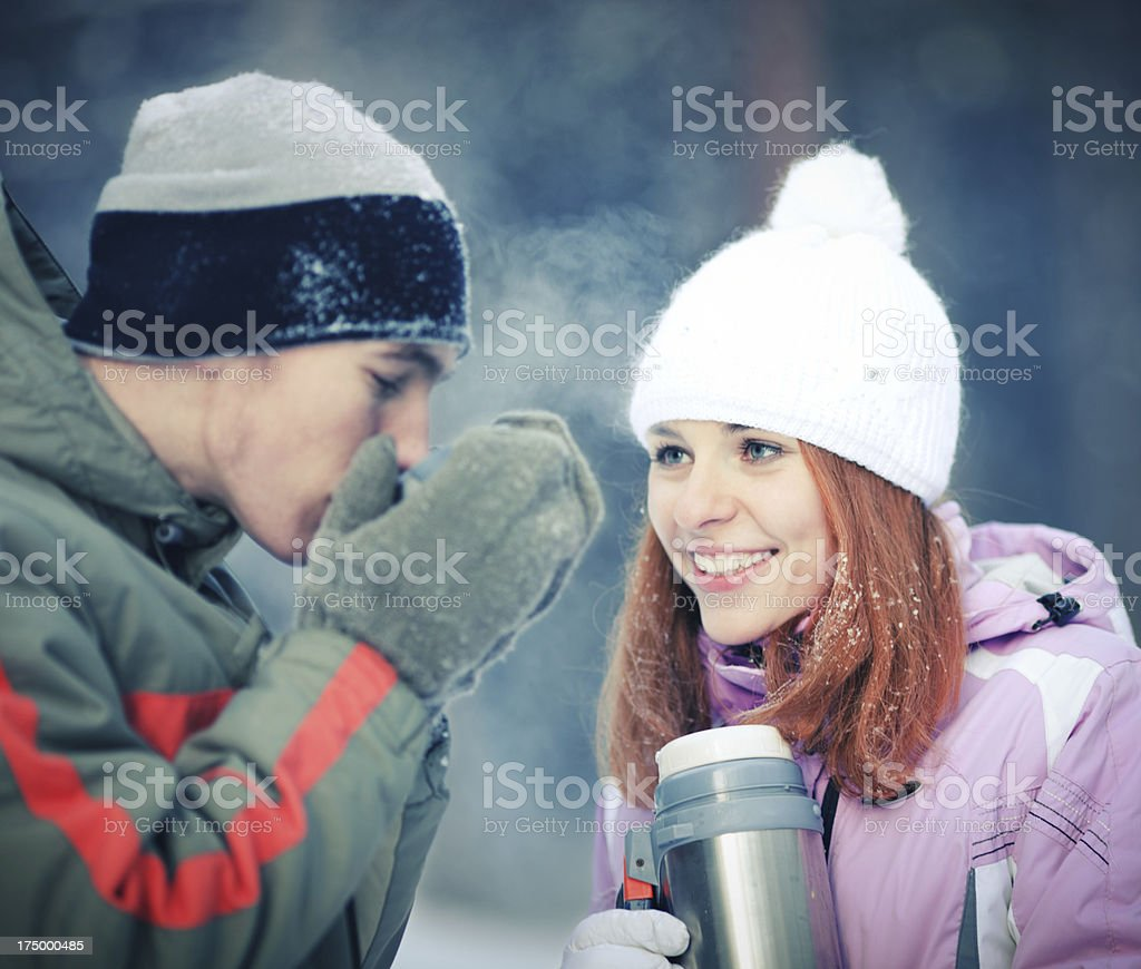 Two teenagers drink tea in winter forest royalty-free stock photo