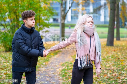 91482522 istock photo Two teenagers in love in quarrel. The blonde girl takes offense at boy, guy holds her hand, asks the girl to stay and not leave. Concept of difficulties in adolescent relationships 1187121584