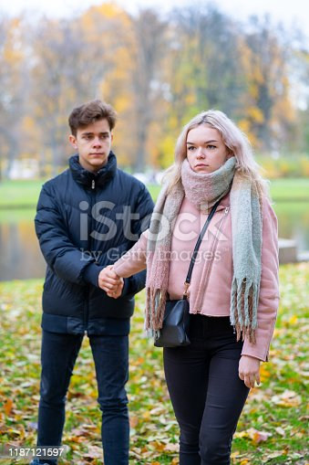 91482522 istock photo Two teenagers in love in quarrel. The blonde girl takes offense at boy, the guy holds her hand, asks the girl to stay and not leave. Concept of difficulties in adolescent relationships 1187121597