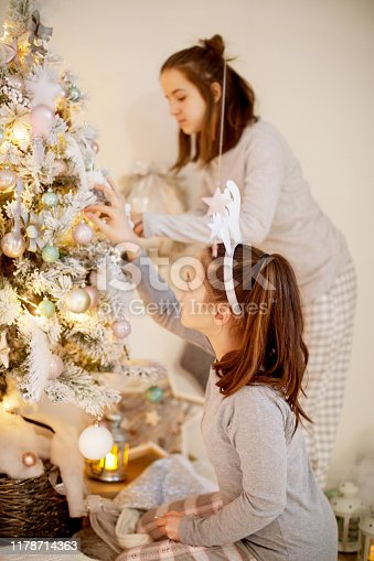 Two teenage girls in pajamas decorating the Christmas tree with care