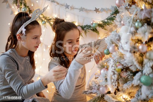 Two teenage girls in pajamas carefully decorating the Christmas tree