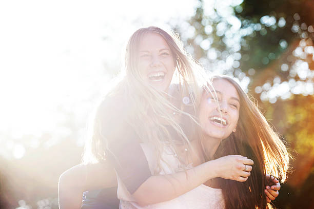Two teenagers laughing at the park stock photo