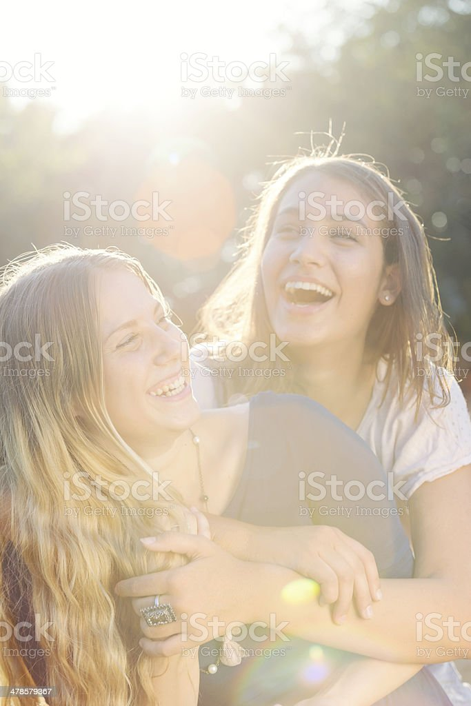 Two teenagers laughing in the park stock photo