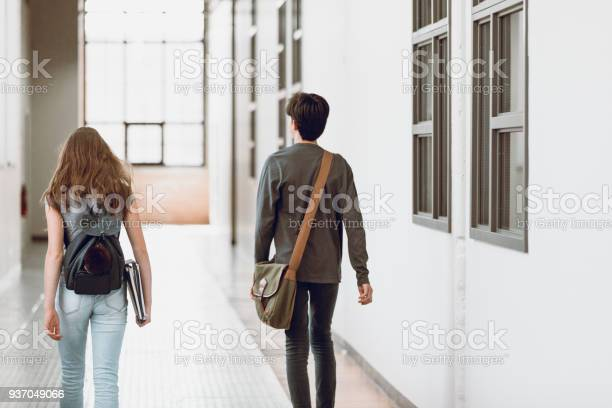 Two teenagers walking in the corridor at school rear view one boy and picture id937049066?b=1&k=6&m=937049066&s=612x612&h=kywrwahrtobfijo77z3igztlbicdsmpgmrgpkspkhvy=