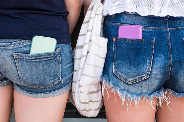 Dois Teenagrs em Shorts com telefones celulares - foto de acervo