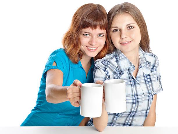 Two teen-girls are drinking tea stock photo