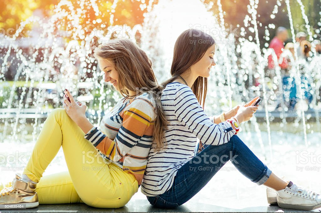 Two teens texting stock photo